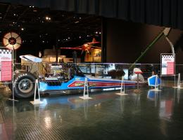Race cars and motorcycles on display include the Wheeler Dealer Dragster.